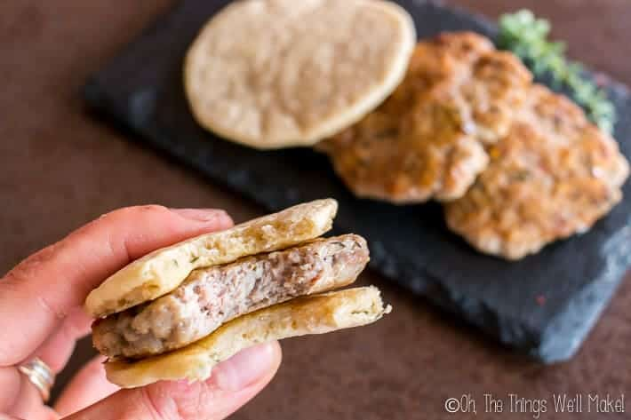 A homemade sausage patty between two paleo pitas being eaten like a sausage biscuit