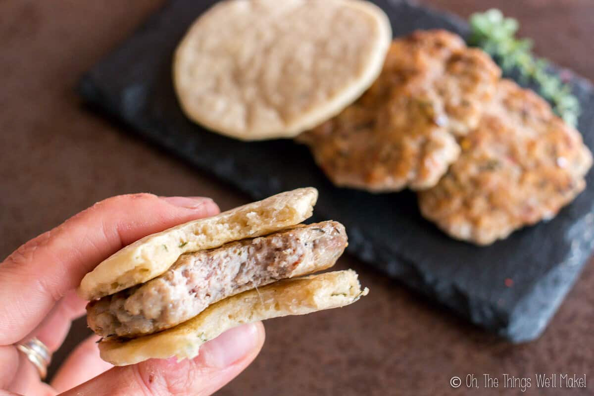 Close up of hand holding a homemade sausage patty between two paleo pitas with a plate of sausage patties and pitas in the background.