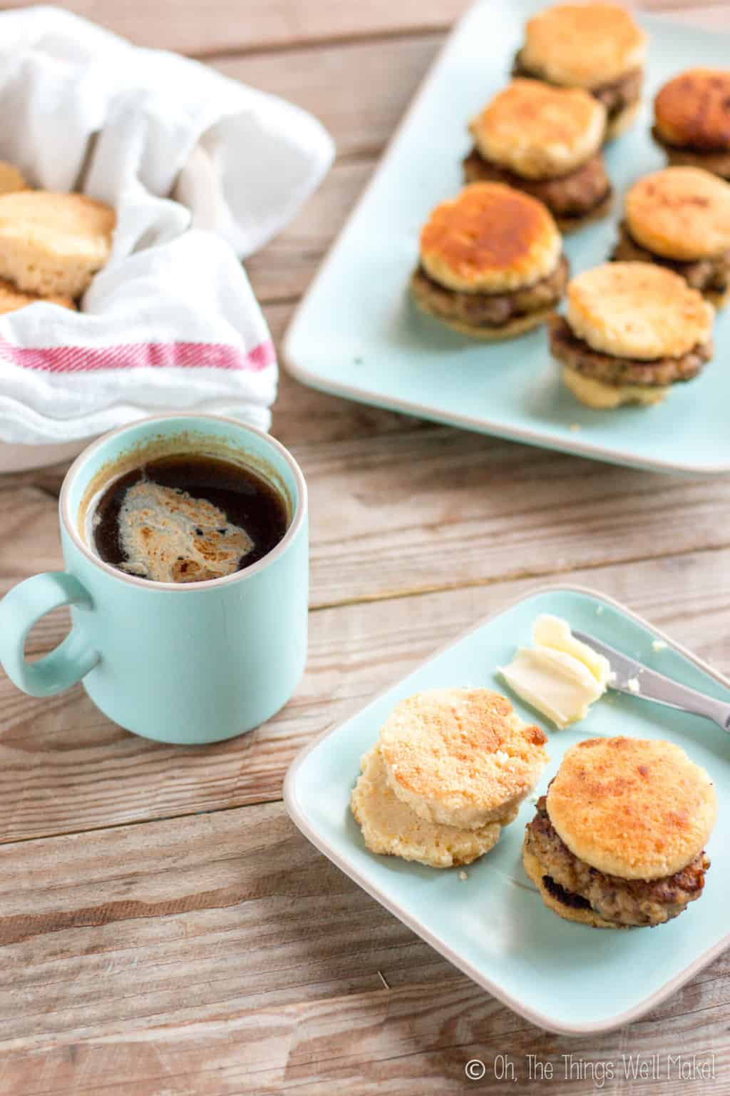 In the foreground, is a light blue square plate with one sausage biscuit and a couple of biscuit pieces next to a knife with butter. A cup of coffee is placed beside it with a bowl of biscuits and another plate of sausage biscuits in the background.v