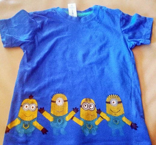 A blue t-shirt with minions across the bottom on a table
