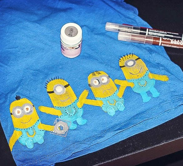 Closeup of painted minions across the bottom of a blue t-shirt.