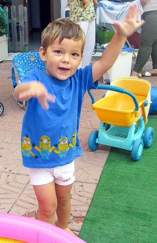 A young boy wearing a blue t-shirt with minions across the bottom.