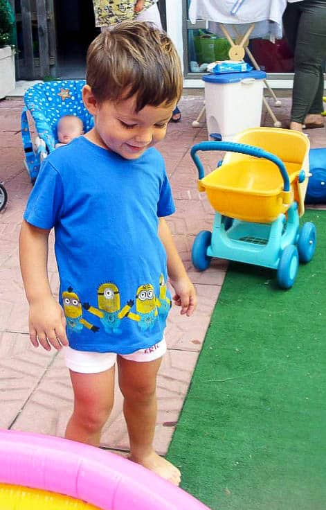 A young boy wearing a blue t-shirt decorated with painted minions at the bottom.