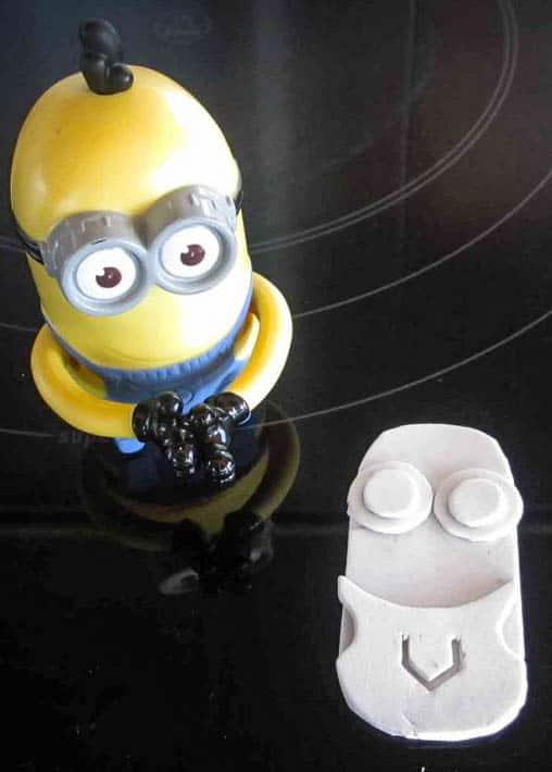 Closeup of several shapes cut out of craft foam (in the form of a minion) next to a plastic minion toy