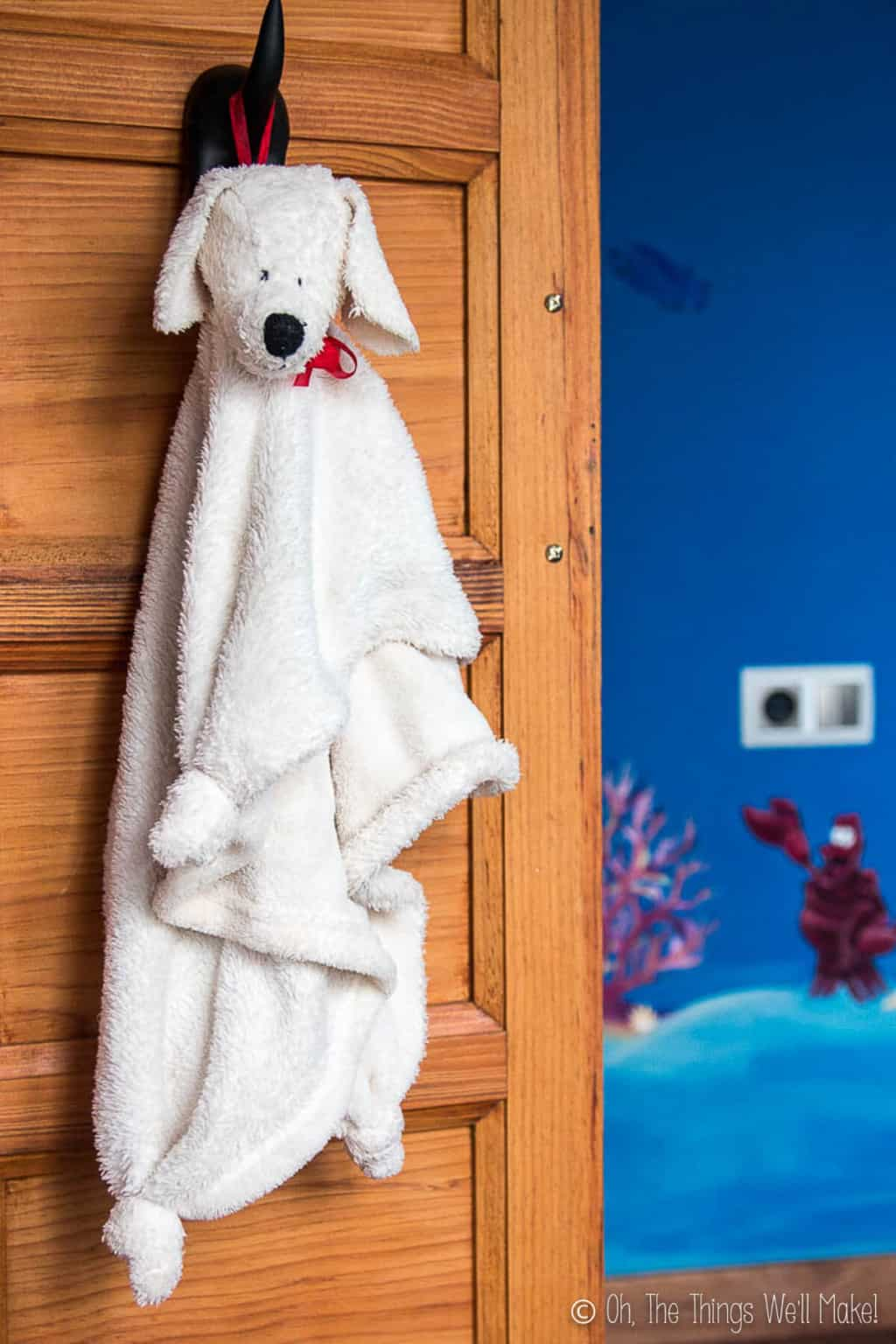 A white fluffy puppy blanket with a stuffed puppy head hanging from the hook on a wood closet door.
