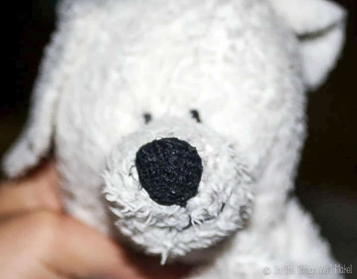 Close up of a hand holding the head of a white fluffy stuffed dog showing the black nose and eyes.