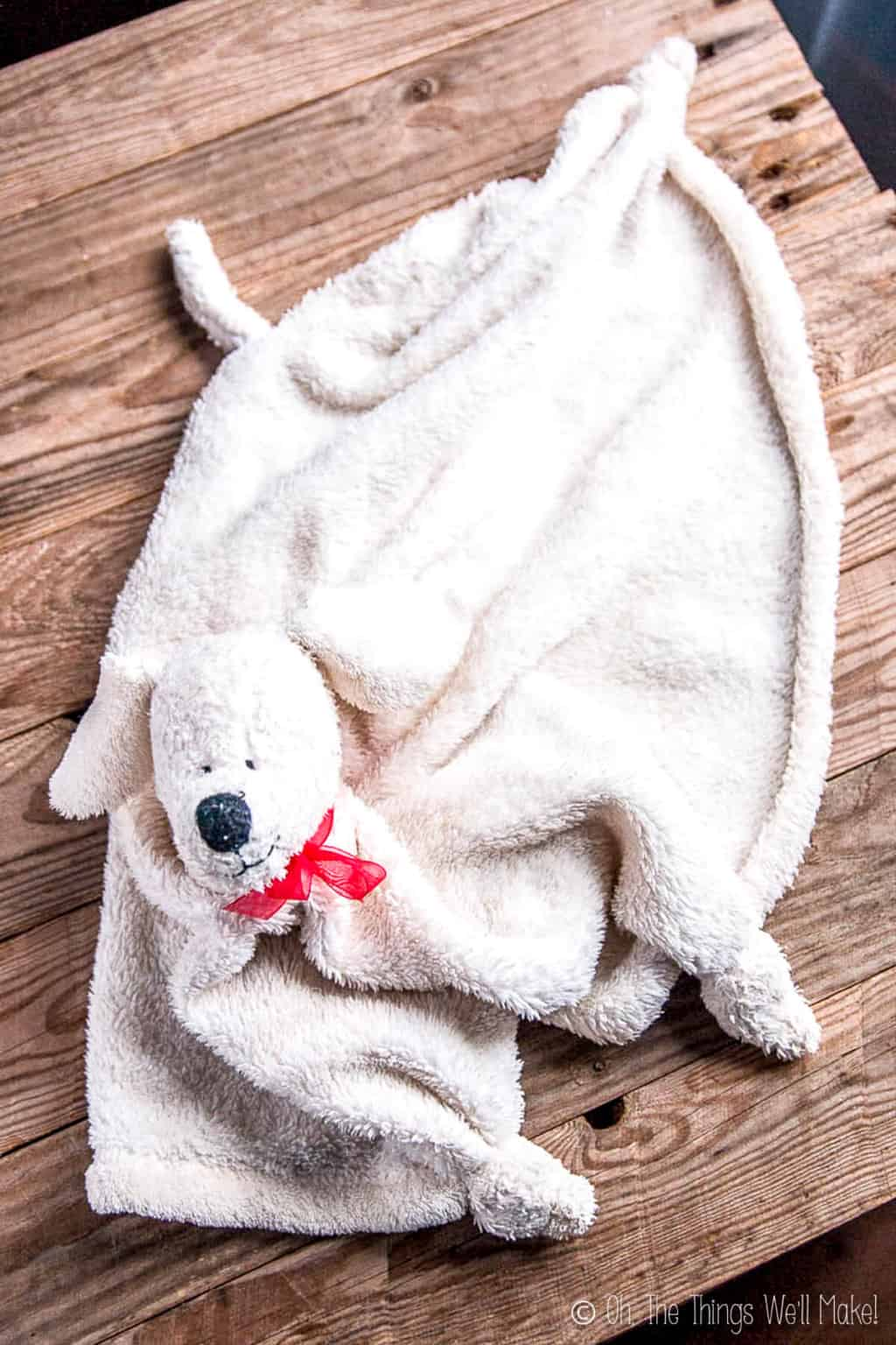A white fluffy blanket with stuffed animal puppy head spread out on a wooden surface that shows off the head, tail, and corners of the blanket.
