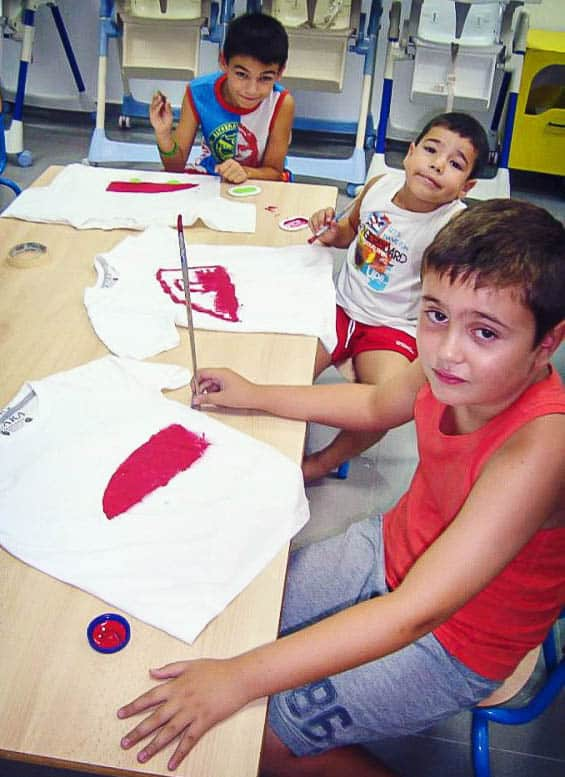 3 boys sitting at a table and painting red cars on their shirts.