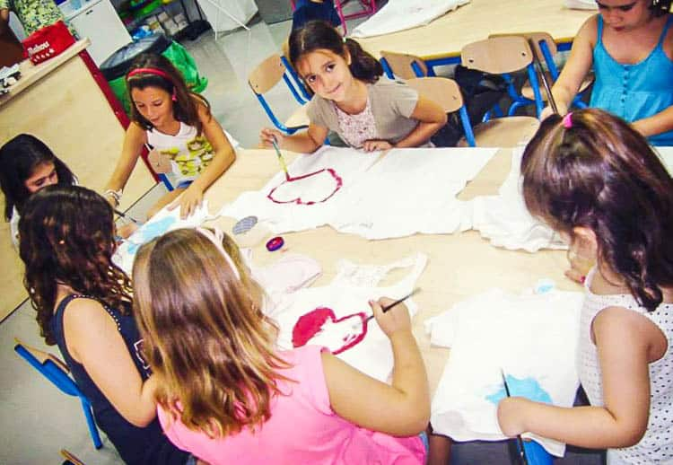 A group of girls sitting at a table and painting hearts on t-shirts