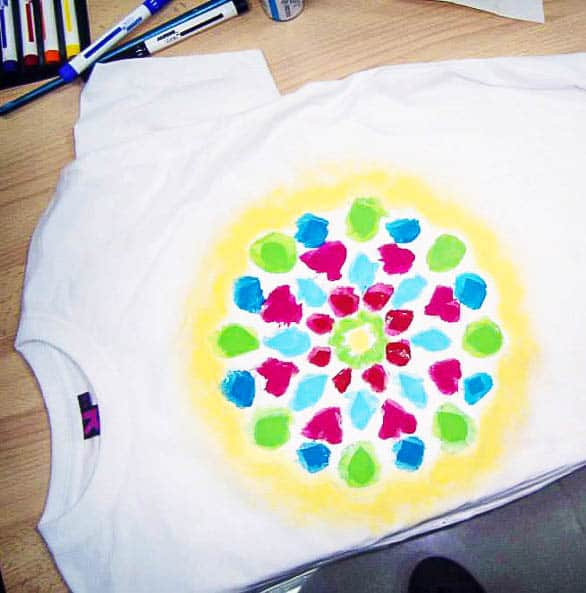 A t-shirt with a freezer paper stencil on it that has been painted with many colors of fabric paint