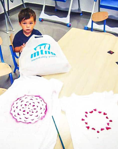 Mandala painting isn't difficult using freezer paper to make stencils. This technique allows even young kids to make beautiful designs. We used the idea to paint t-shirts, but you can also use it to paint other fabrics or materials.