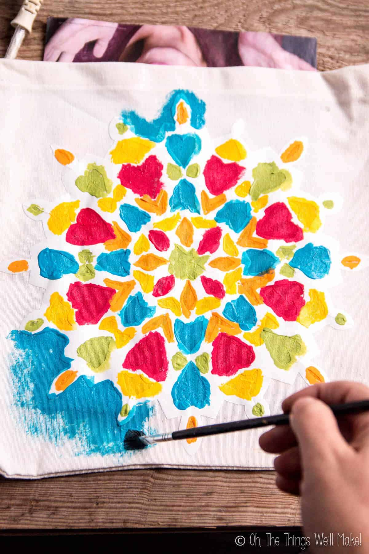 Painting on a paper snowflake stencil that has been adhered to a cloth bag, making a colorful, mandala-like design.