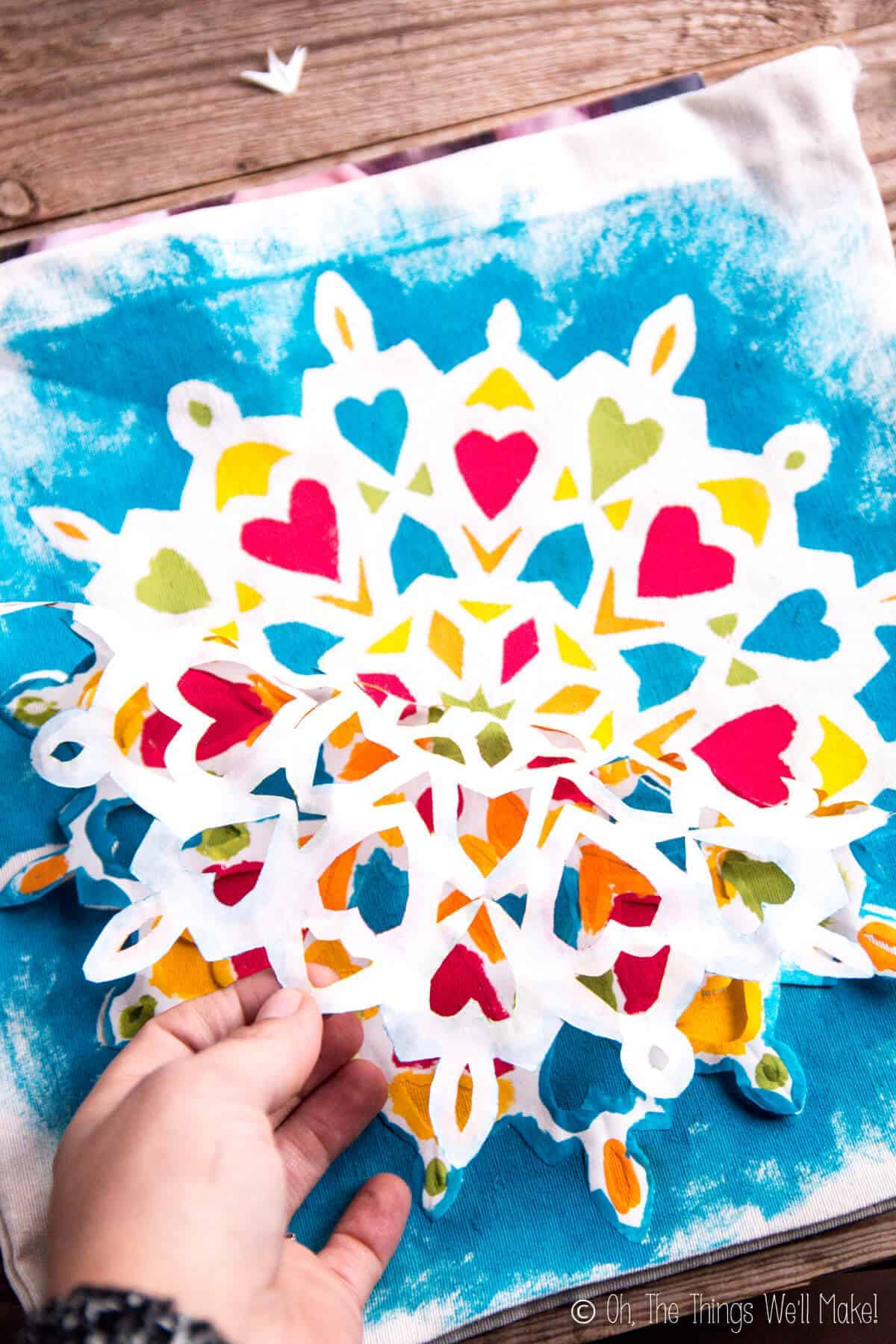 Peeling off the freezer paper snowflake stencil to reveal a beautiful mandala painted on a fabric bag.