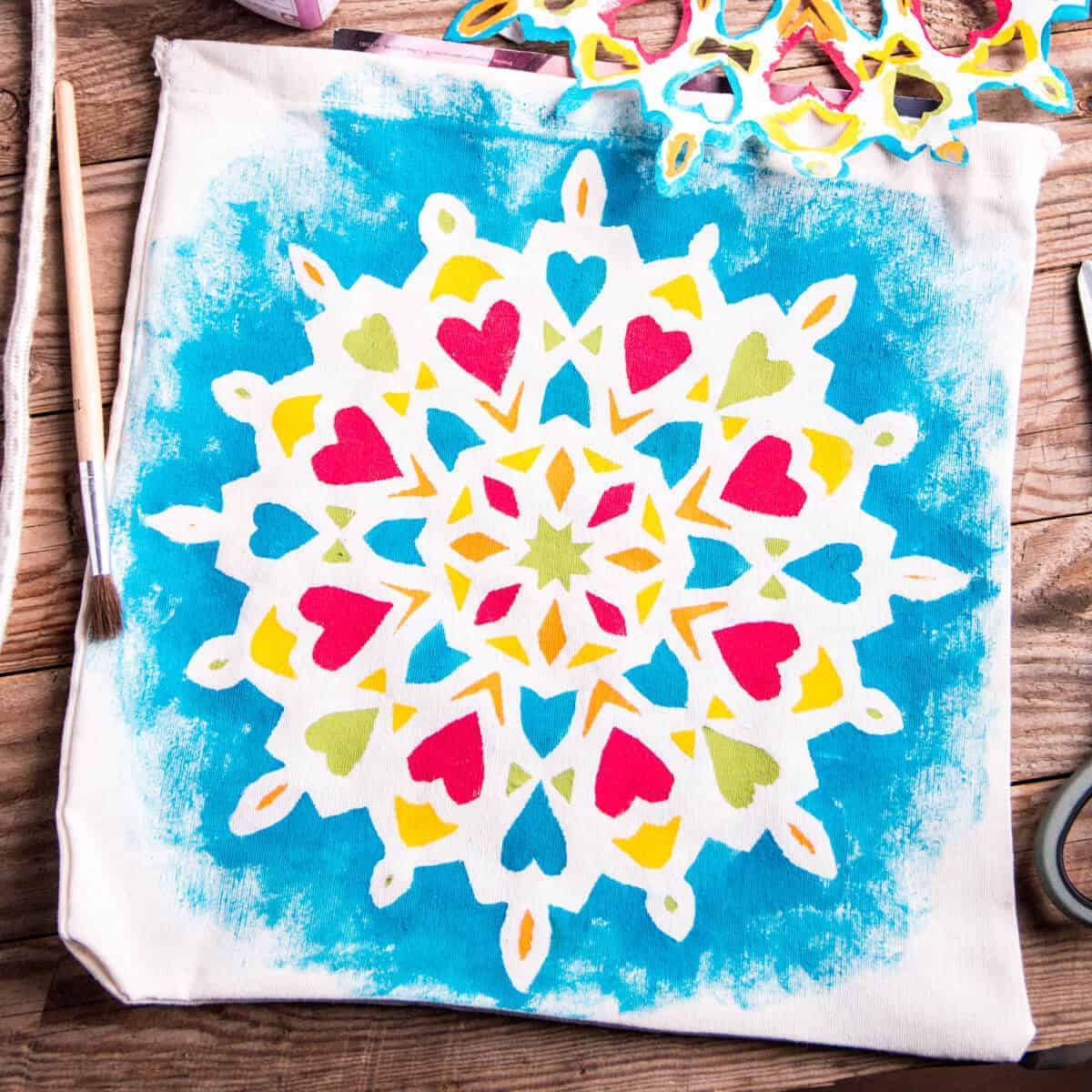A cloth bag with a beautiful colorful mandala design painted on it with fabric paints.