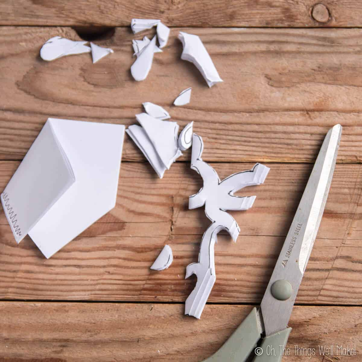 A paper snowflake being cut out from a folded piece of paper.