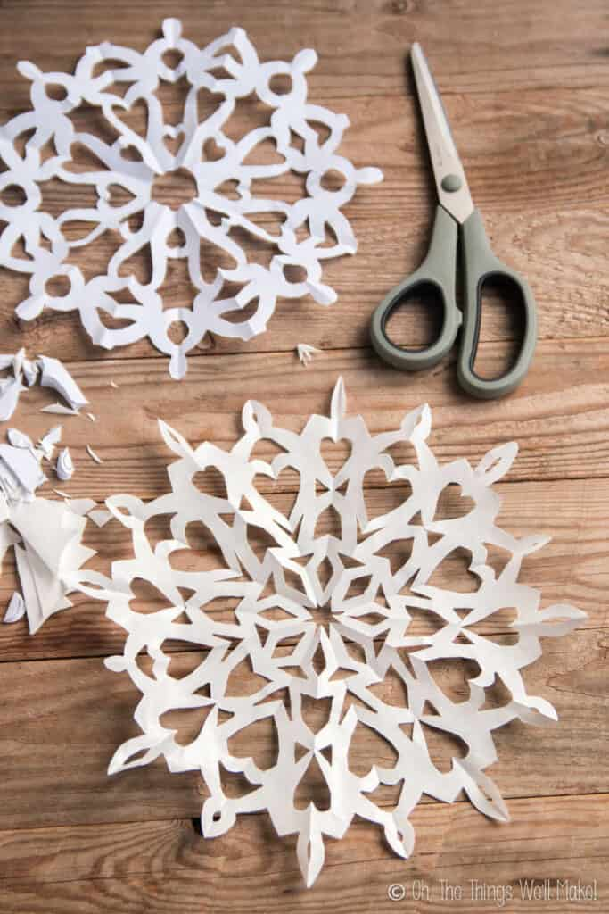 two round paper snowflakes with hearts in a mandala type shape on a wooden background.