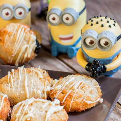 A closeup of delicious coconutties drizzled with white chocolate on a black plate, surrounded by small Minion toys.