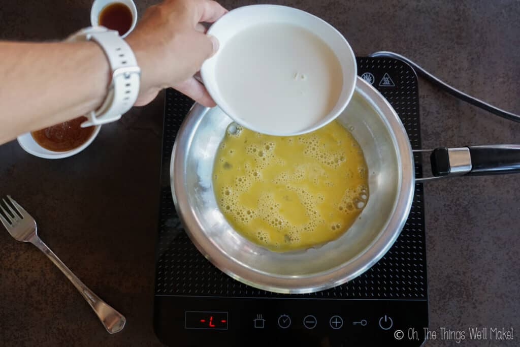 Adding cream to a stainless steel pan with beaten egg.