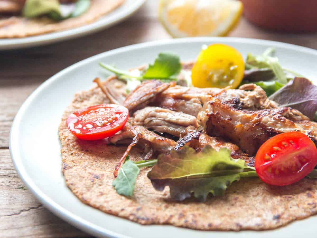 Crispy slow cooked shredded pork carnitas served on a paleo flaxseed tortilla with diced yellow and red tomatoes and greens on a white plate.
