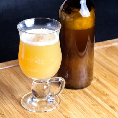 A glass full of yellow homemade hard cider made from kefir grains, next to to a bottle full of the same cider.