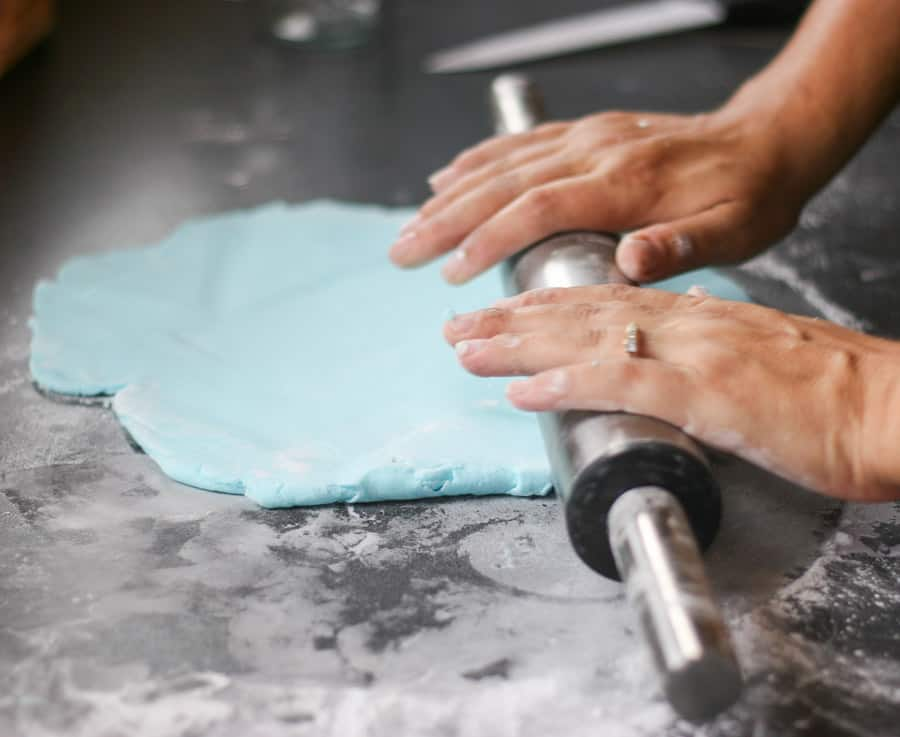 hands rolling out blue fondant with a rolling pin.