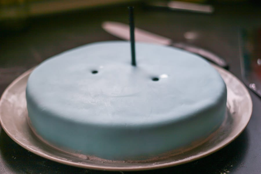 Poking a straw into a fondant cake.
