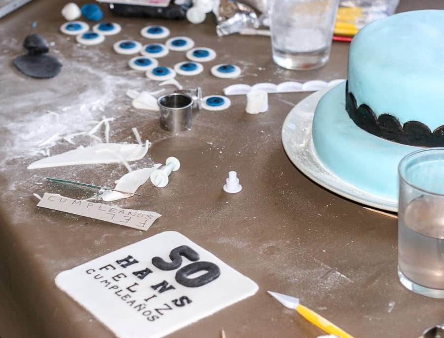 A fondant cake with a fondant eye chart and fondant circles in the foreground.