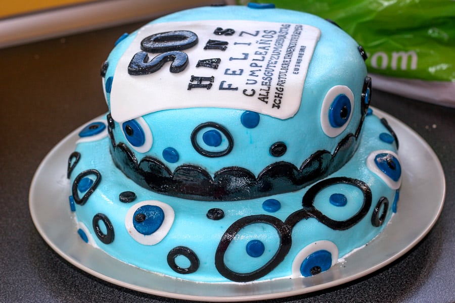 Side view of a fondant optometrist cake that is shiny from water condensation on top.