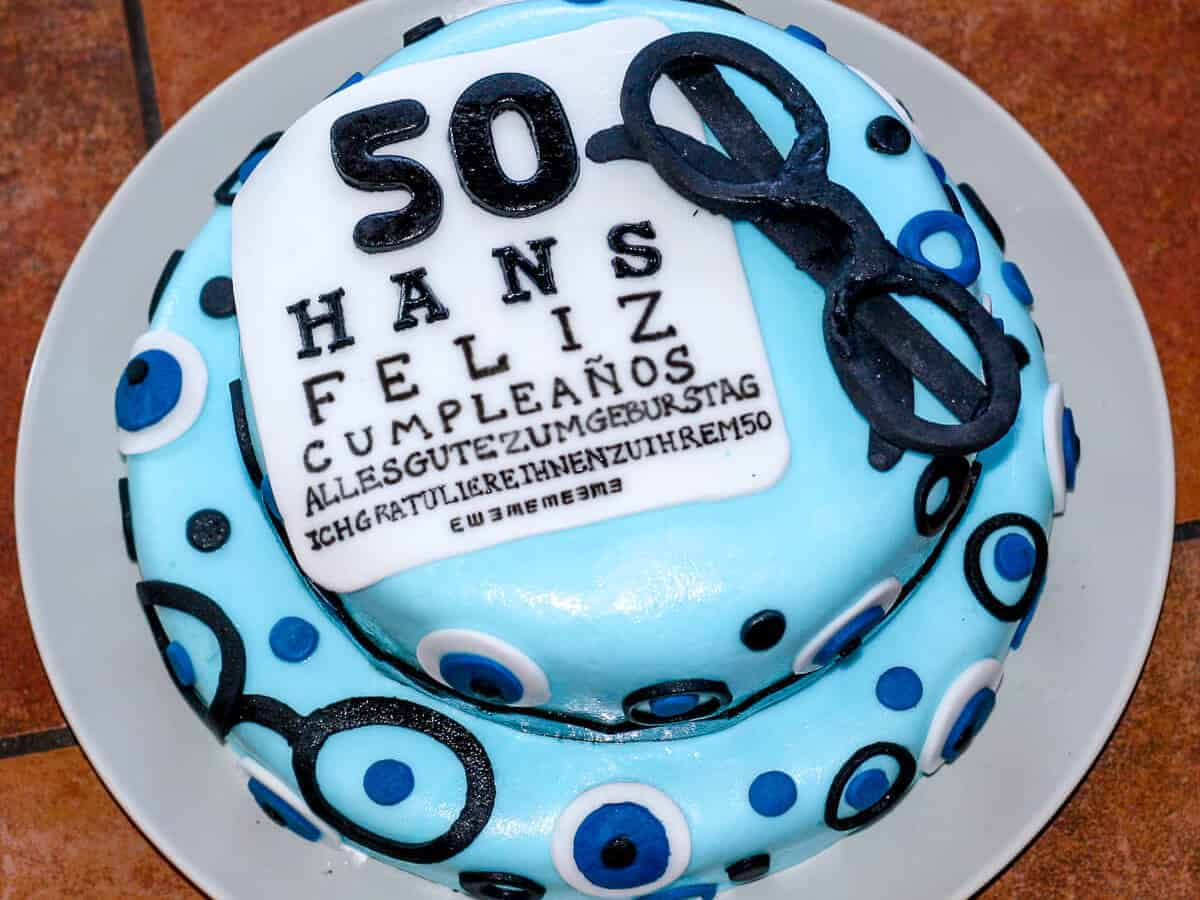 """Overhead view of a fifty year old birthday cake covered in light blue fondant and decorated with fondant decorations of black eyeglasses, eyes, and a birthday greeting that says """"50 hans feliz cumpleanos"""""""