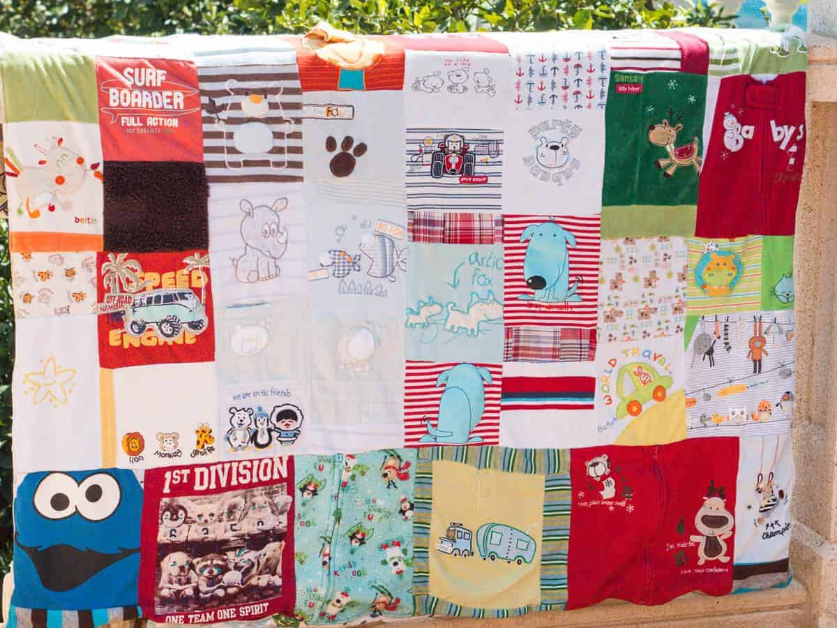 A colorful keepsake quilt made out of old baby clothes placed on a balcony balustrade.