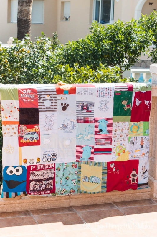 A homemade baby clothes quilt hung over the handrail of a terrace.