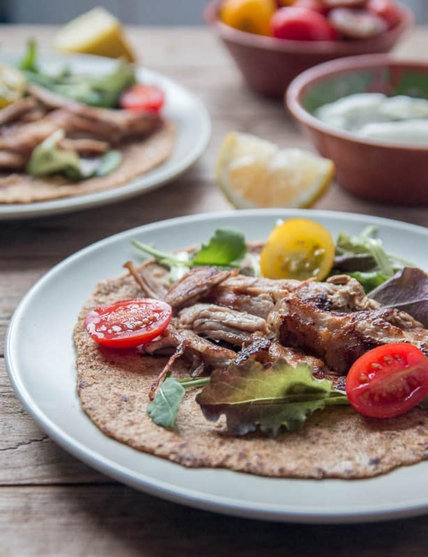 Closeup of crispy pork carnitas with sliced open cherry tomatoes and lettuce on a flaxseed tortilla.