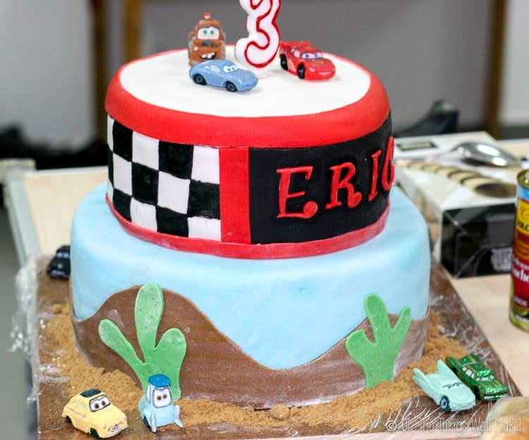 2 tier cake decorated with a Cars movie theme with painted checkerboard and fondant car figures.
