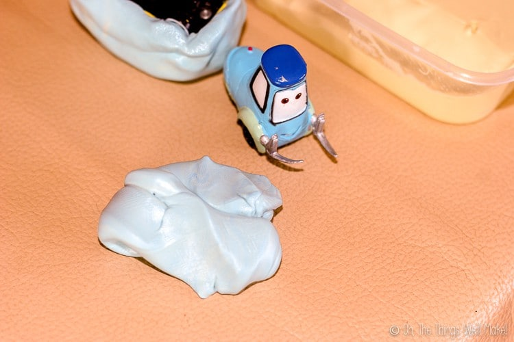 A ball of silicone putty next to a toy of Guido from Cars.