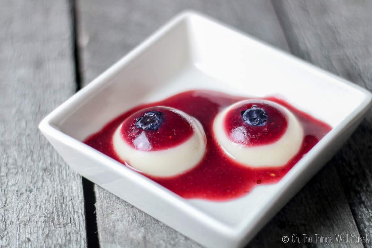 Two gummy eyeballs in a square bowl served with berry puree, placed on a grey wood surface.
