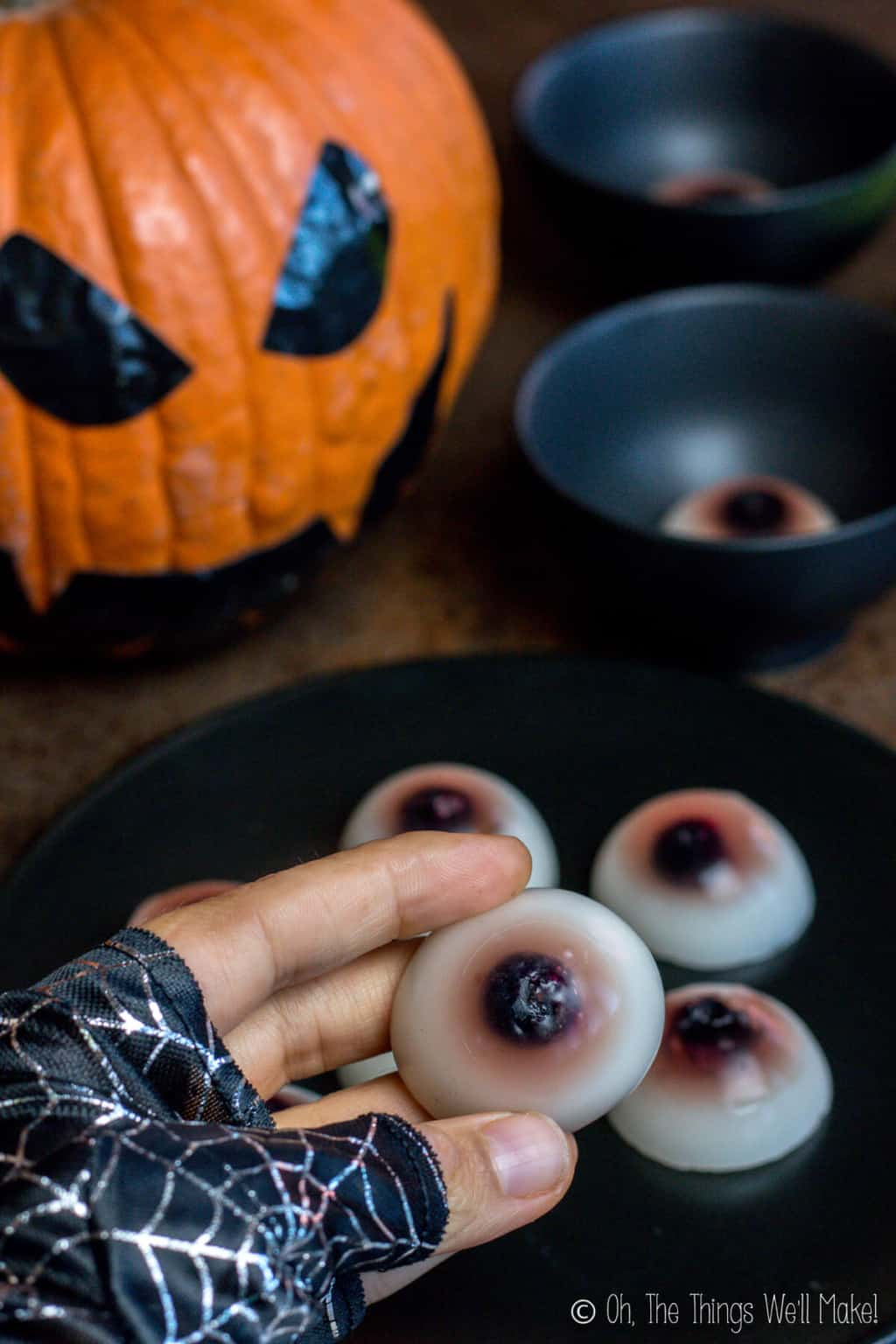 A hand holding a gummy eyeball from a plate full of gummy eyeballs and a jack-o-lantern in the background.