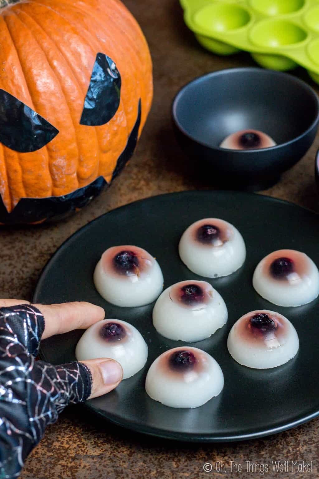A hand about to pick up a homemade gummy eyeball off a plate full of them.