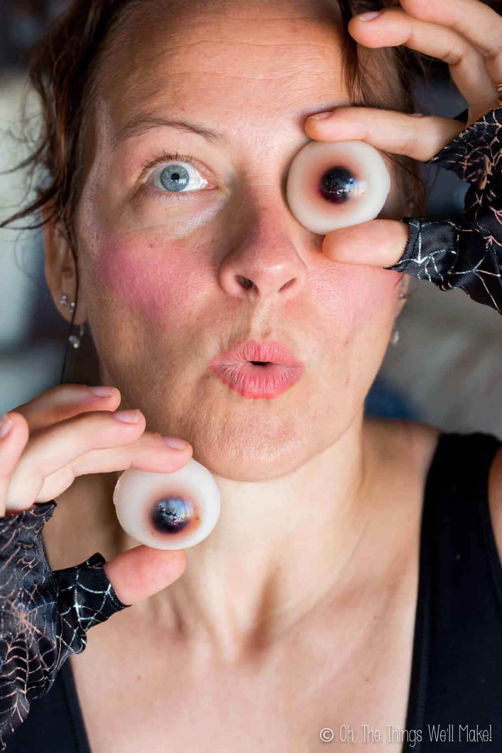 A woman holding up two homemade gummy eyeballs: one against one of her eyes and the other below her face.