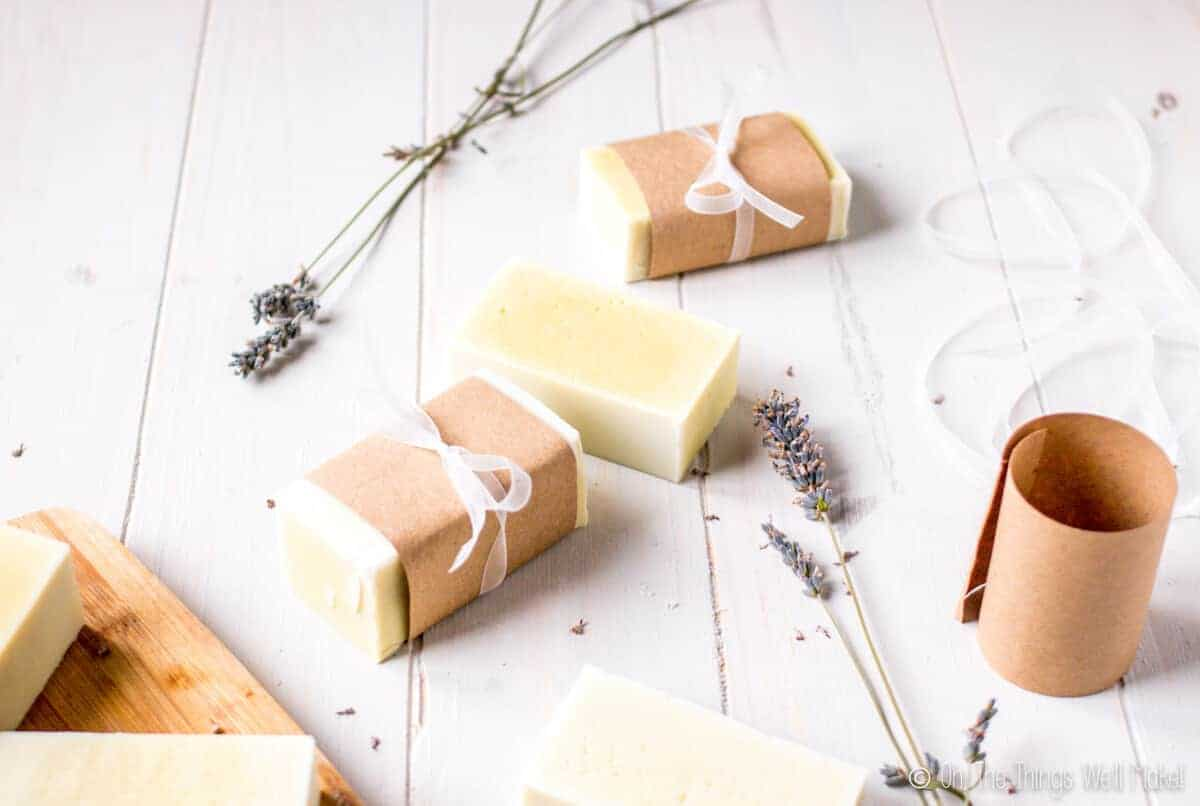 Homemade soap, surrounded by lavender flowers, wrapped with paper and ribbons. Some paper and ribbon are seen on the side.