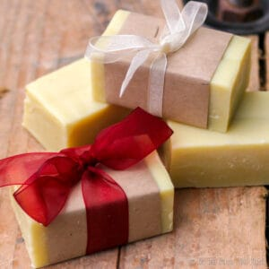 Closeup of 4 bars of homemade soap. Two of them have been wrapped in brown paper and wrapped with ribbons. One soap is wrapped with red ribbon and the other with white ribbon.