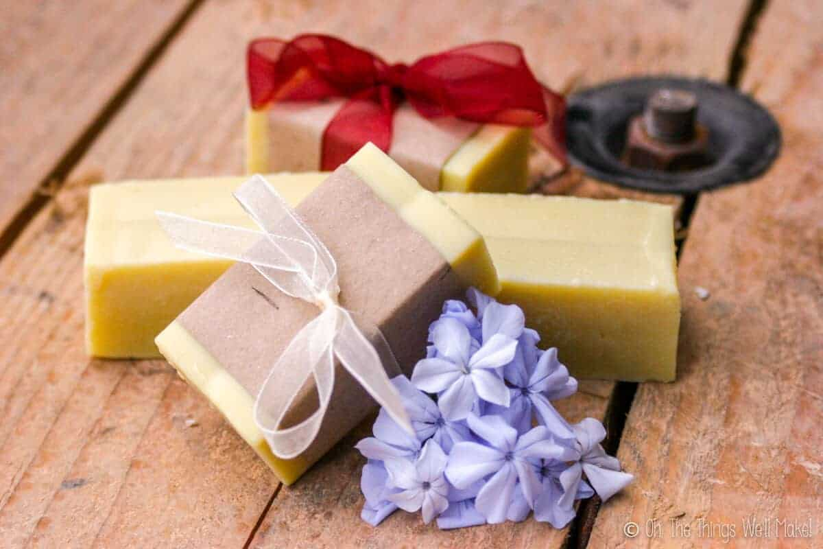 4 bars of homemade soap by some blue flowers. Two are wrapped in paper.