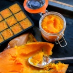 Overhead view of scooping out a roasted butternut squash pumpkin into a jar and ice cube trays for freezing.