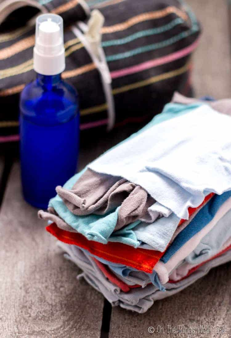 A stack of homemade cloth wipes in front of a bottle of wipe solution
