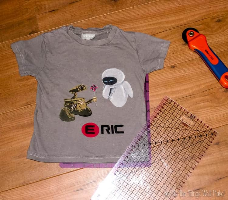 Overhead view of Wall-E t-shirt and a rotary cutter and ruler