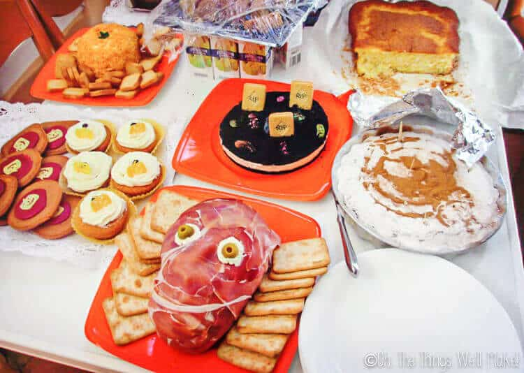 Table with Halloween foods including a prosciuttos face and a pumpkin shaped cheeseball with crackers