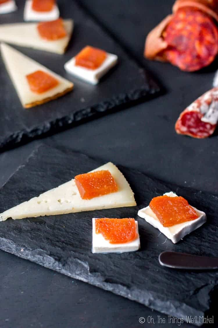 Slices of dulce de membrillo (also known as quince cheese) over slices of different types of cheese.