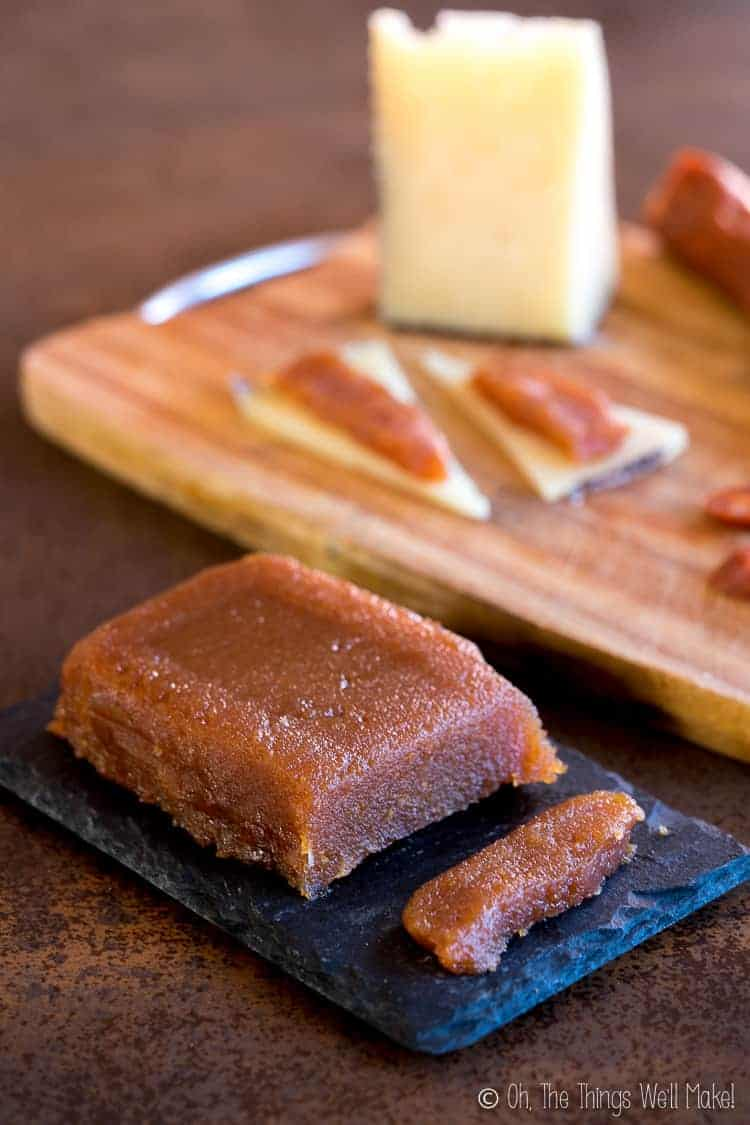membrillo on a platter in front of a cutting board with cheese