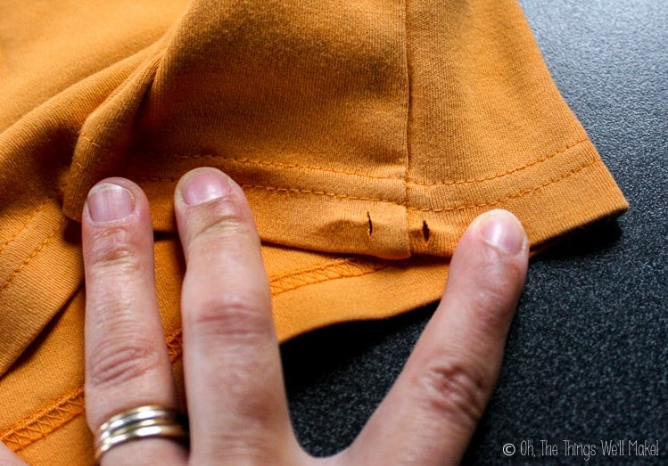 Small slits have been cut into the bottom hem enclosure of the t-shirt on either side of the seam