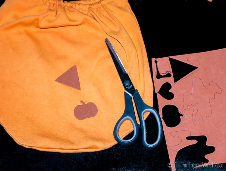 Cutting a triangle and Halloween themed shapes from craft foam to make fabric stamps