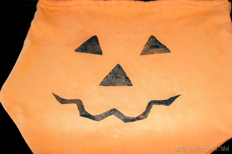 stamping a Jack-o-lantern face onto our homemade trick-or-treat bag